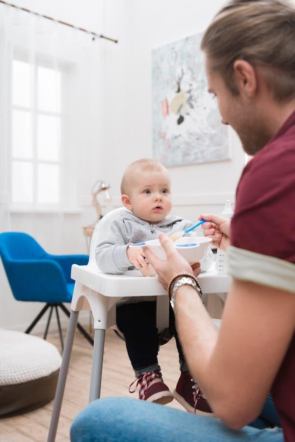 Vati, der seinen kleinen Sohn mit Säuglingsnahrung einzieht lizenzfreie stockfotografie