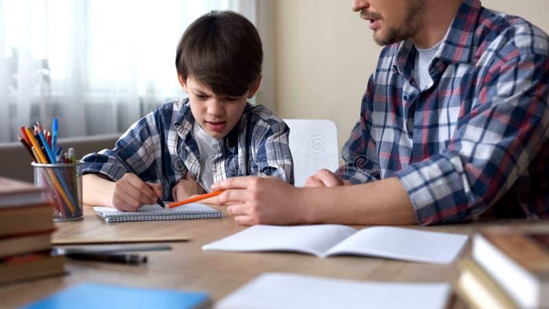 Vati, der am Tisch sitzt und seinen launischen Sohn Hausarbeit, Bildung tun lässt stockfotografie