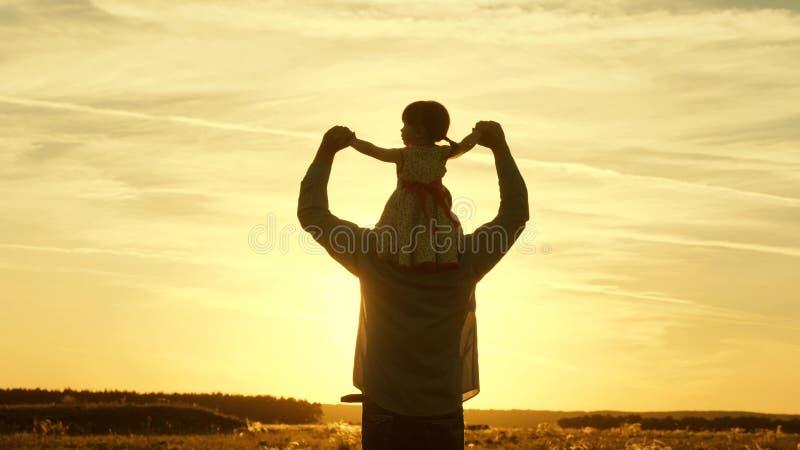 Vati macht Schultern seines geliebten Kindes, in den Strahlen der Sonne weiter Vater geht mit seiner Tochter auf seinen Schultern stockbilder