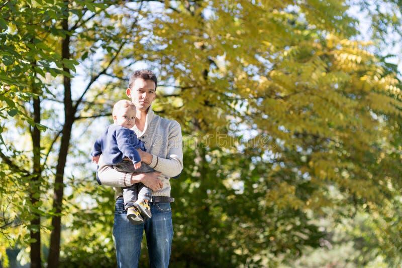 Vati mit Baby im Herbstpark lizenzfreie stockbilder
