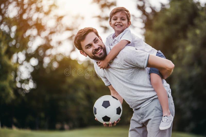 Vati mit dem Sohn, der Fußball spielt stockbild