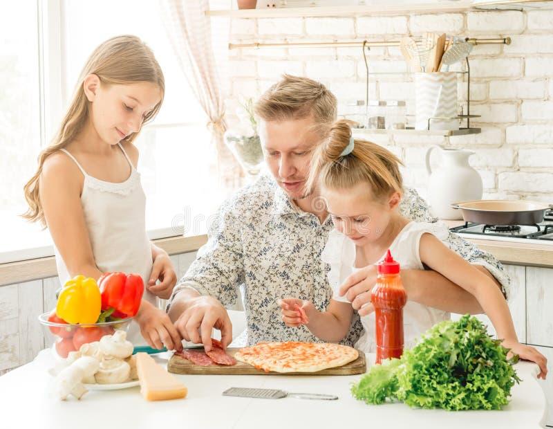Vati mit den Töchtern, die Pizza zubereiten lizenzfreie stockfotos