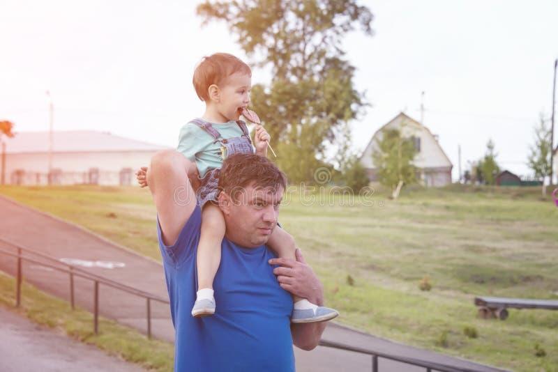 Vati mit einem Kind auf seinen Schultern während eines Wegs lizenzfreies stockfoto