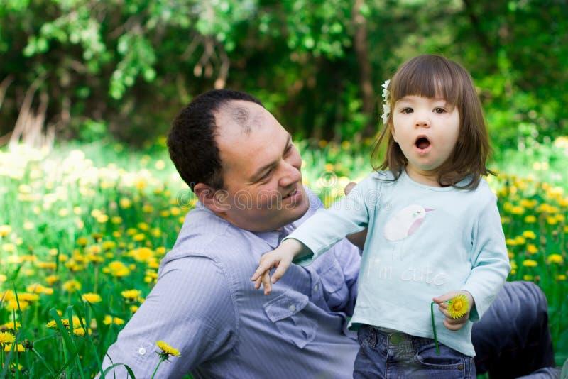 Vati mit einer kleinen Tochter, die Spaß im Park hat lizenzfreies stockfoto