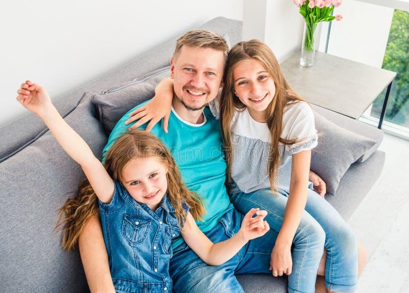 Vati mit Töchtern genießen Wochenenden zuhause lizenzfreies stockbild