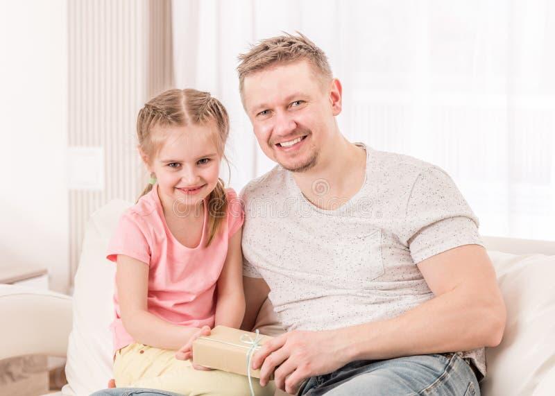 Vati mit Tochter ?ffnendem Vatertagsgeschenk auf Sofa stockbilder