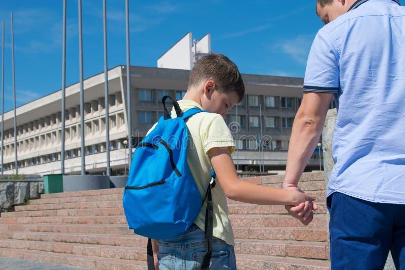 Vati nimmt seinen Sohn zur Schule, die Studentenblicke auf seine Vaterhand stockfoto