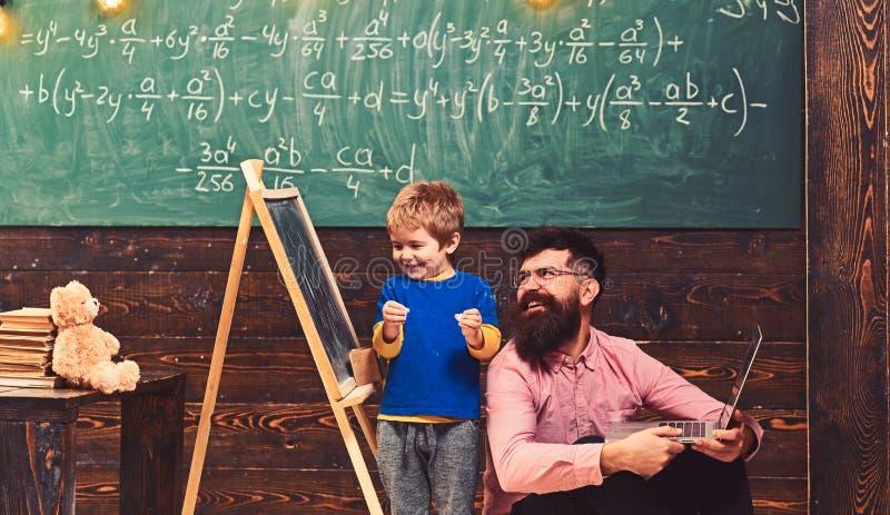 Vati und Kind, die beim Lernen von neuen Sachen lachen L?chelnder Lehrer und Sch?ler, die gl?ckliches Kind des Spa?es zusammen in lizenzfreie stockfotografie