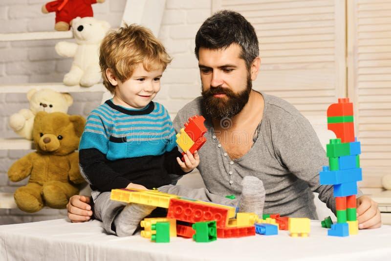 Vati und Kind mit Spielwaren auf Hintergrundgestalt von Bl?cken lizenzfreies stockfoto