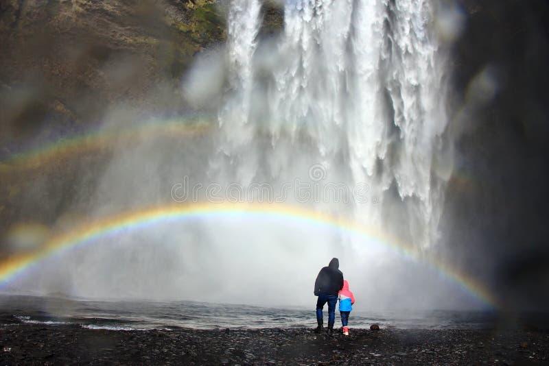 Vati und Kind unter dem Regenbogen am Fuß schweren Wasserfalls Skogafoss in Island lizenzfreies stockfoto