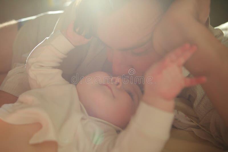 Vati und sein Sohn Ein Mann nahe bei einem neugeborenen Baby Männliche Bildung und Liebe Neugeboren in der Krippe Brutpflegekinde stockbild