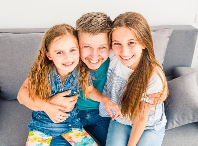 Vati und seine zwei lächelnden Töchter stockfoto