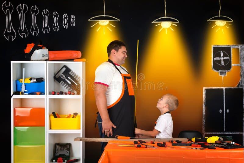 Vati und Sohn arbeiten in der Werkstatt zusammen stockfoto