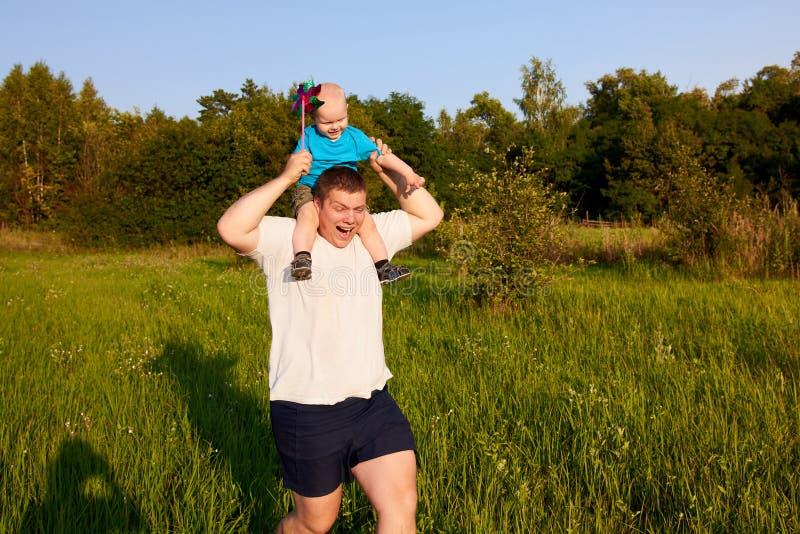Vati und Sohn, die Spaß in der Natur im Sommer, Vater hält sein Kind auf seinen Schultern mit Feuerrad hat stockfotografie