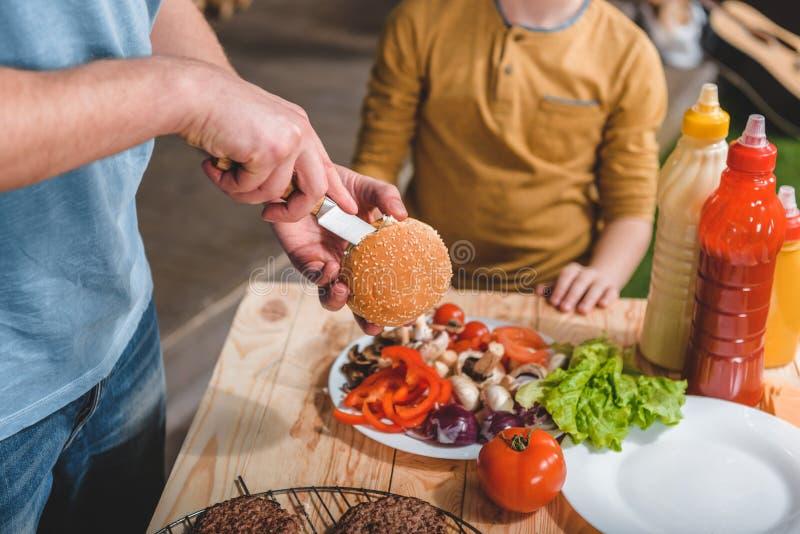 Vati und Sohn, die zusammen Fleischburger kochen stockfotografie