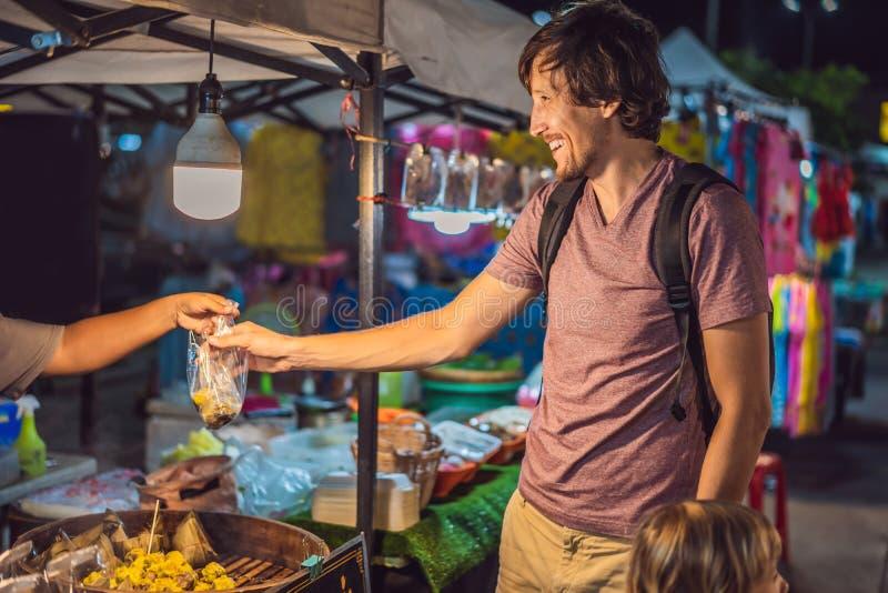 Vati und Sohn sind Touristen auf gehendem asiatischem Markt der Stra?e Nahrungsmittel lizenzfreie stockfotografie