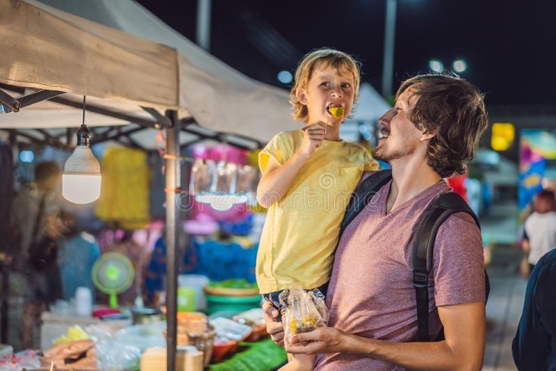 Vati und Sohn sind Touristen auf gehendem asiatischem Markt der Stra?e Nahrungsmittel stockfotografie