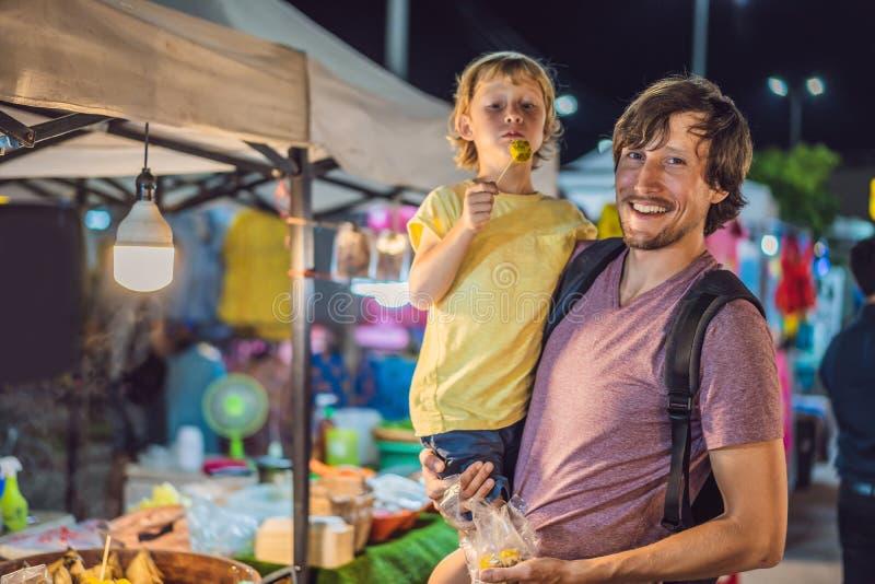 Vati und Sohn sind Touristen auf gehendem asiatischem Markt der Stra?e Nahrungsmittel lizenzfreies stockfoto