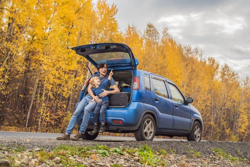 Vati und Sohn stehen auf der Seite der Stra?e auf einer Autoreise still Autoreise mit Kinderkonzept stockbild