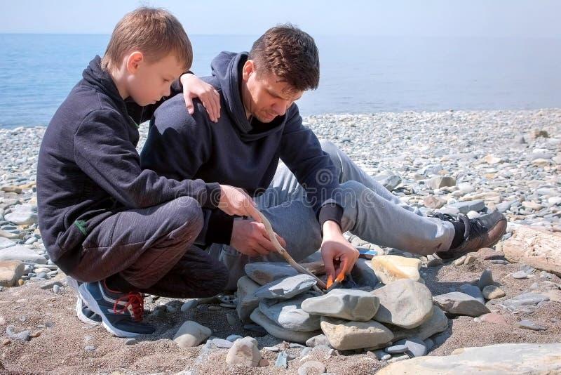 Vati und Sohn zünden die Kohlen im Feuer auf dem handgemachten Steinmessingarbeiter auf Seestrand an Vater und Sohn, die eine Kar lizenzfreies stockbild