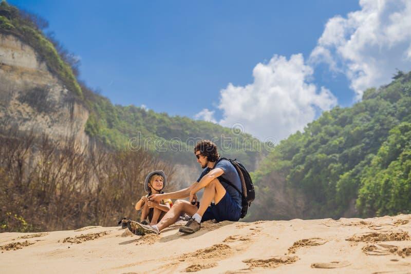 Vati- und Sohnreisende auf dem Überraschen von Melasti-Strand mit Türkiswasser, Bali-Insel Indonesien Reisen mit Kinderkonzept stockbild