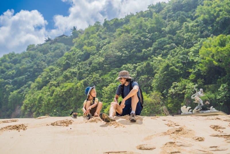Vati- und Sohnreisende auf dem Überraschen von Melasti-Strand mit Türkiswasser, Bali-Insel Indonesien Reisen mit Kinderkonzept stockfotografie