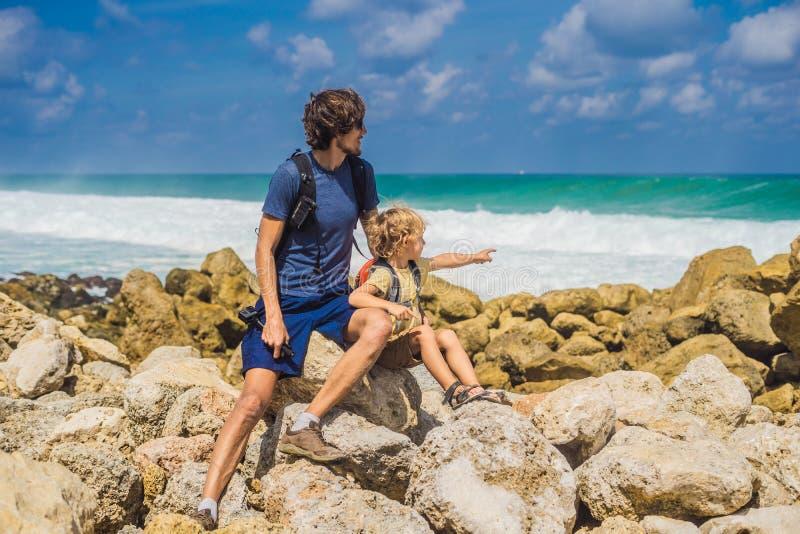 Vati- und Sohnreisende auf dem Überraschen von Melasti-Strand mit Türkiswasser, Bali-Insel Indonesien Reisen mit Kinderkonzept stockfoto