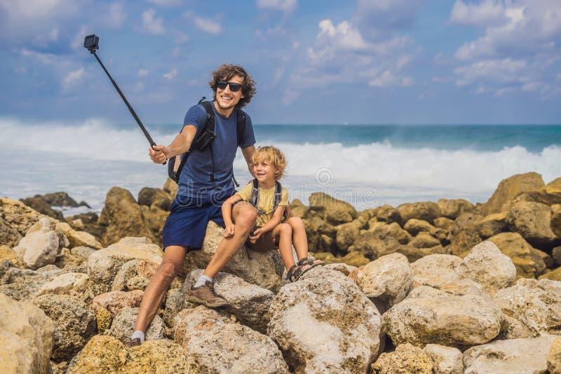 Vati- und Sohnreisende auf dem Überraschen von Melasti-Strand mit Türkiswasser, Bali-Insel Indonesien Reisen mit Kinderkonzept lizenzfreie stockfotos