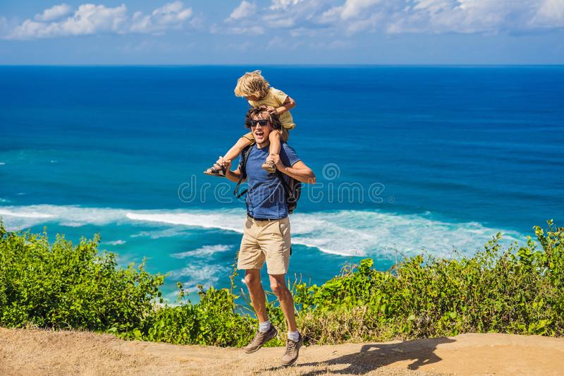Vati- und Sohnreisende auf einer Klippe über dem Strand Leeres Paradies stockbilder