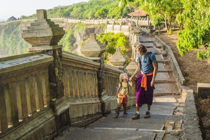 Vati- und Sohnreisende in Pura Luhur Uluwatu-Tempel, Bali, Indonesien Erstaunliche Landschaft - Klippe mit blauem Himmel und Meer stockfoto