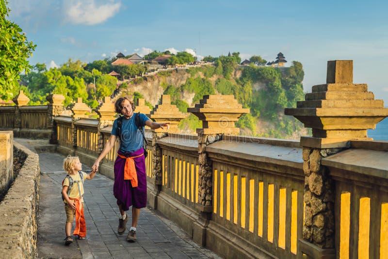 Vati- und Sohnreisende in Pura Luhur Uluwatu-Tempel, Bali, Indonesien Erstaunliche Landschaft - Klippe mit blauem Himmel und Meer lizenzfreie stockfotos