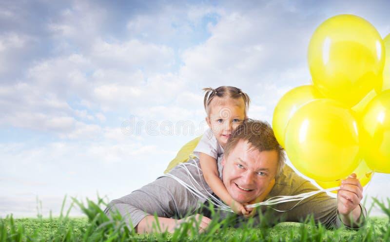 Vati und Tochter auf dem Gras stockfoto