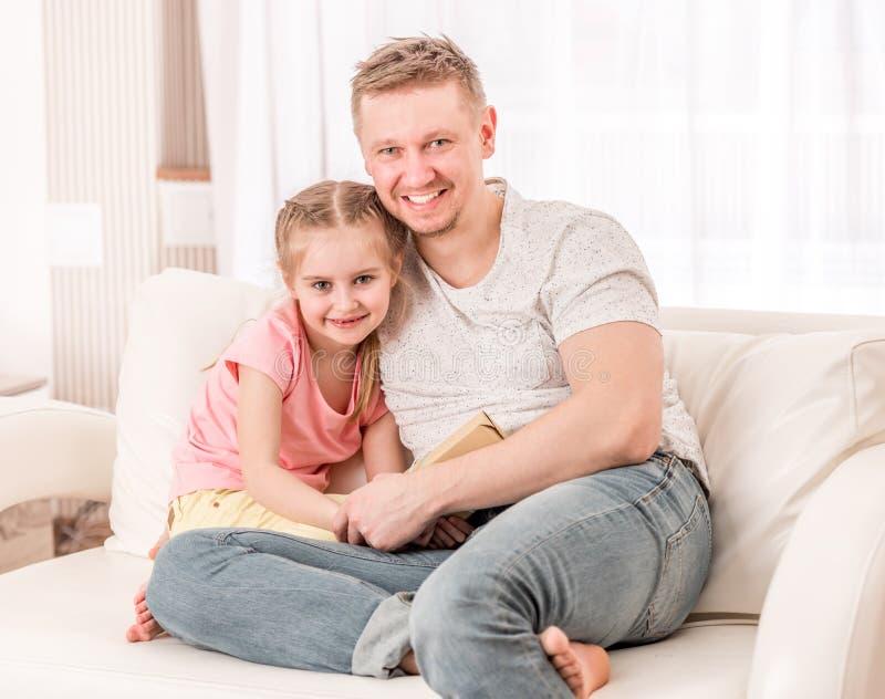 Vati und Tochter, die auf der Couch sitzen lizenzfreies stockbild