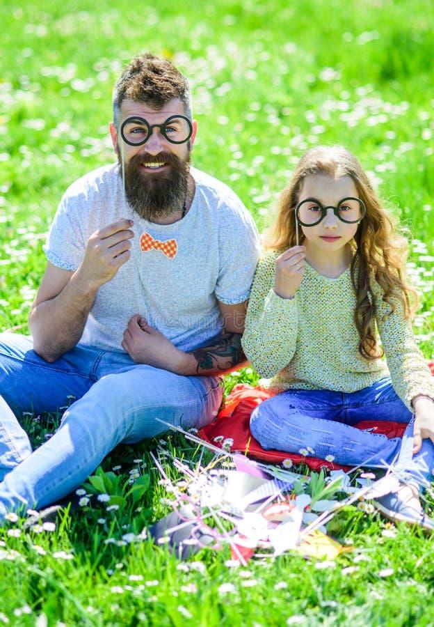 Vati und Tochter sitzt auf Gras am grassplot, grüner Hintergrund Kind und Vater, die mit eyeglases Passfotoautomaten aufwerfen stockfotos