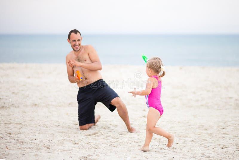 Vati und Tochter spielen Wasserpistolen auf dem Meer lizenzfreies stockbild