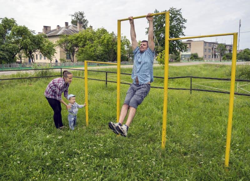 Vati zeigt Übungen auf der Stange für seinen Sohn stockfoto