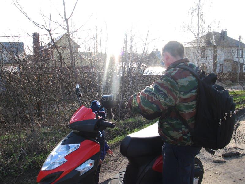 Vati zeigt seinem Sohn ein gro?es rotes Motorrad lizenzfreie stockfotos