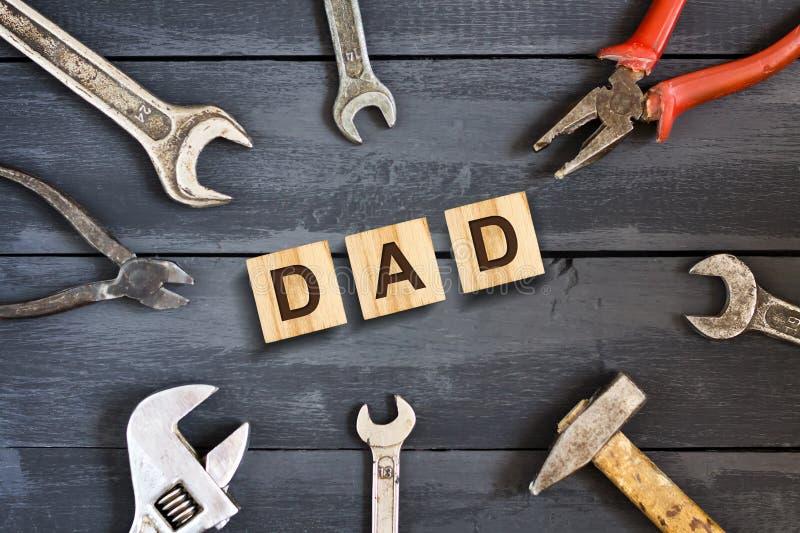 Vatiaufschrift auf hölzernen Würfeln mit Arbeitsgeräten auf einem hölzernen Hintergrund Glücklicher Vatertag Grüße und Geschenke stockfoto