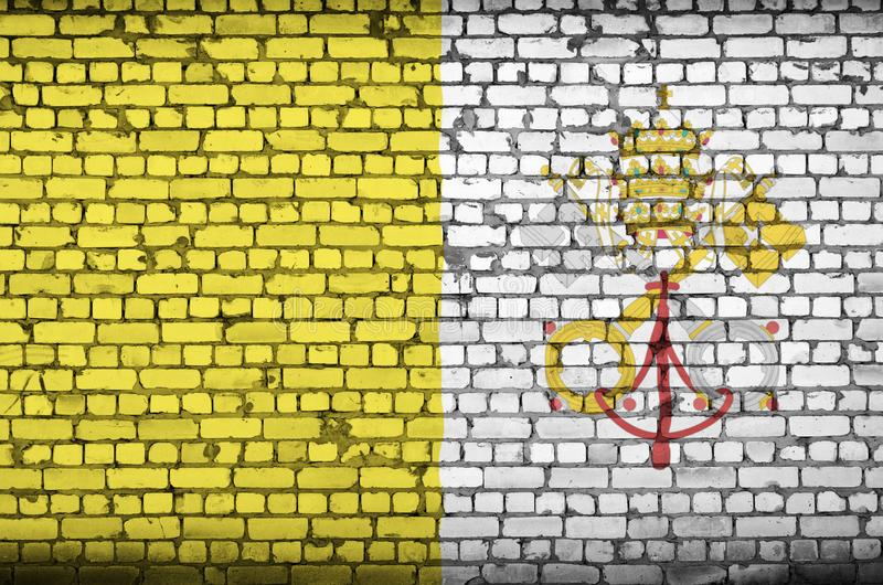 Vatican City State flag is painted onto an old brick wall royalty free stock photo