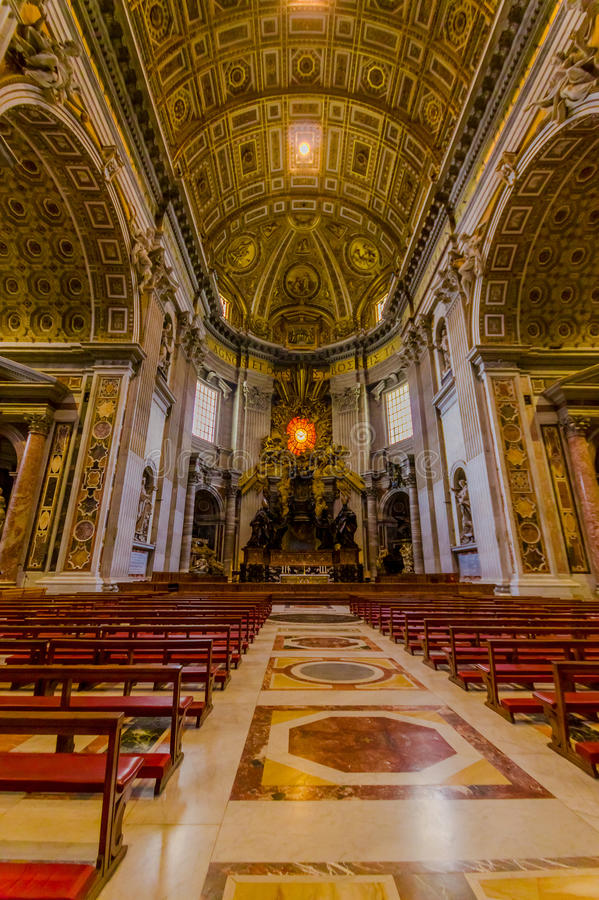 VATICAN, ITALY - JUNE 13, 2015: Altar inside Saint Peter basilica in Vaticano, nobody on the red chairs. Large beautiful royalty free stock image