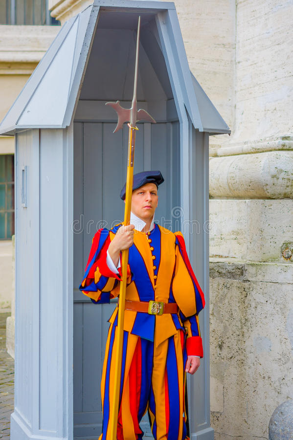 VATICAN, ITALY - JUNE 13, 2015: Swiss guard outside of Basilica at Vatican. Colorful and striped uniform considered one stock photo