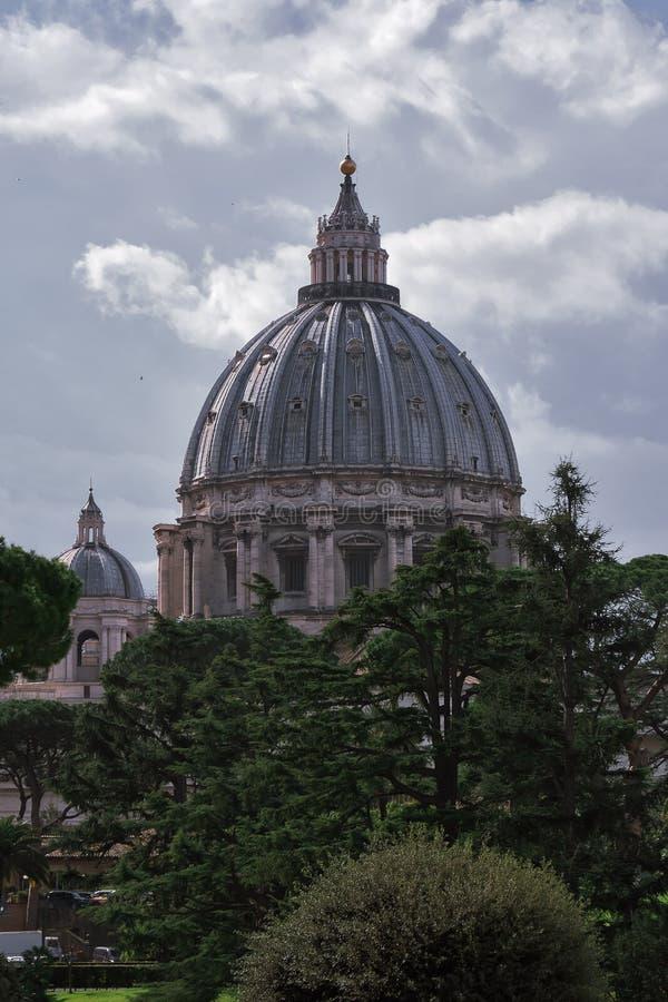 VATIKAN - März 2019: Vatikan arbeitet Ansicht mit St Peter Basilikahaube hinter den Bäumen, Vatikan, Rom im Garten stockfoto