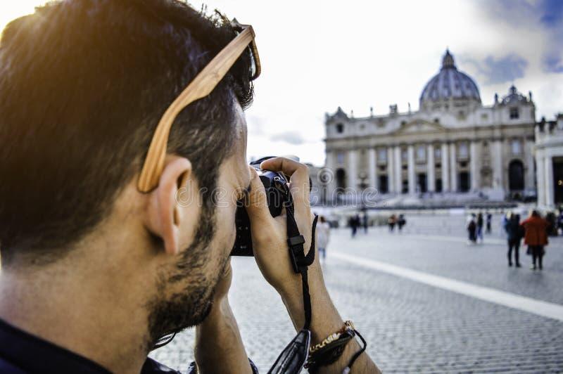 Vatikanstadt, Rom, Italien Junger Mann, der Foto von St Peter Quadrat mit der berühmten Basilika im Hintergrund macht stockbild