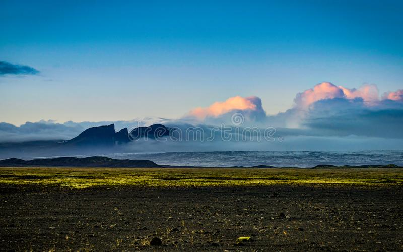 Vatnajokull Glacier covered in fog with mountains and blue sky royalty free stock photo
