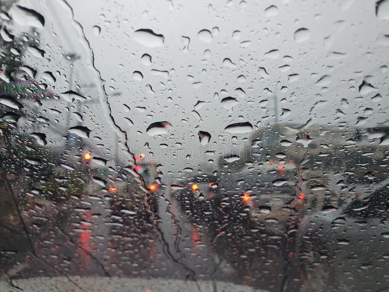 Vatten faller framför bilspegeln med otydlig trafik på väg under skoldagar royaltyfria bilder