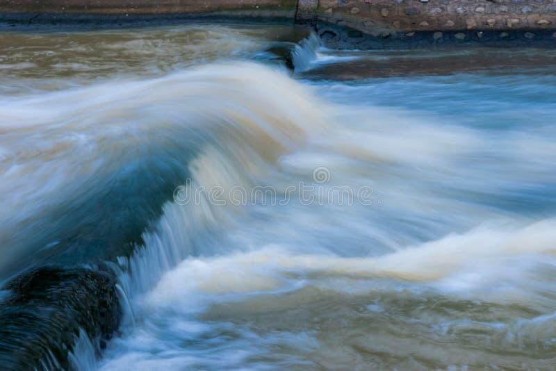 Vatten flödar över fördämningen royaltyfri bild