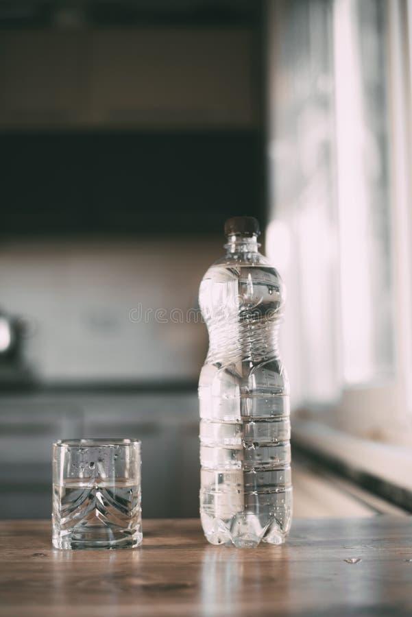 Vatten i en flaska och ett exponeringsglas på tabellen hemma i köket arkivbild