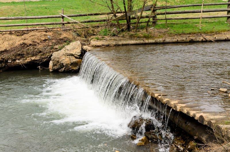 Vatten i en ström som kör över en dammbyggnad arkivfoto
