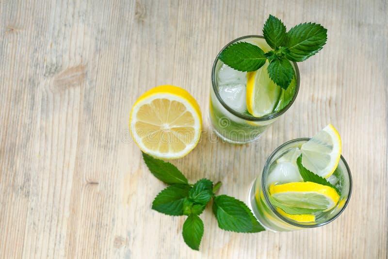 Vatten med citronen, mintkaramellsidor och is i exponeringsglas på en trätabell Citron filialer av mintkaramellen ovanför sikt ko arkivbild