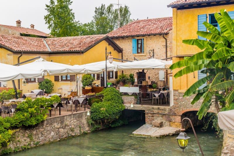 Vatten och forntida restaurang av den italienska medeltida byn royaltyfria bilder